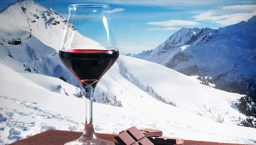 Wine glass and chocolate with winter mountainscape