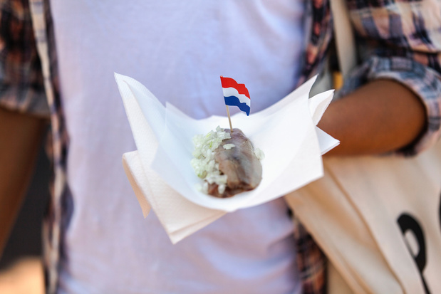 Woman holding napking with matjes herring and Dutch flag